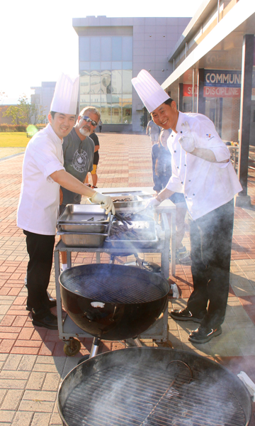 Cafeteria cooks grilling for students