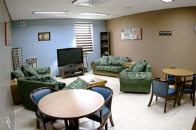 A dorm television room, just off of the main common area, with seating for many people